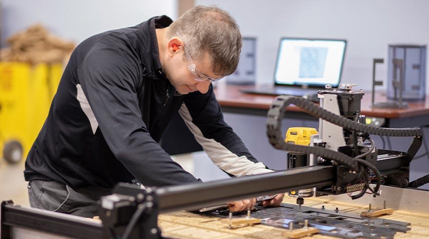 Man in lab usitng cutting machine