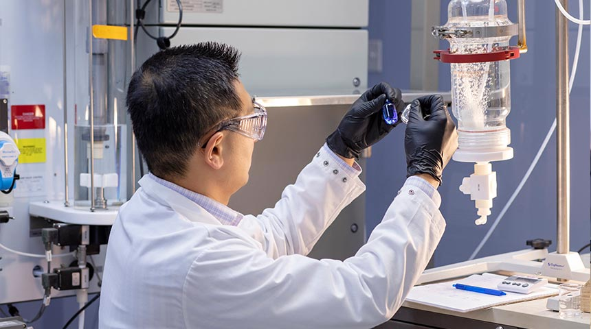 Lab technician looking at solutions in two vials